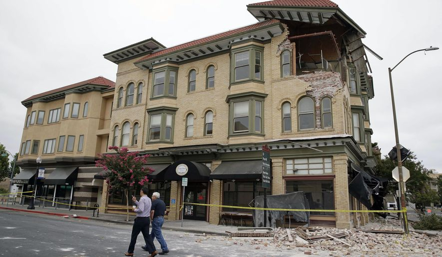 Two men walk past the earthquake-damaged building that housed the Carpe Diem wine bar  Monday, Aug. 25, 2014, in Napa, Calif. The San Francisco Bay Area's strongest earthquake in 25 years struck the heart of California's wine country early Sunday, igniting gas-fed fires, damaging some of the region's famed wineries and historic buildings, and sending dozens of people to hospitals. (AP Photo/Eric Risberg)