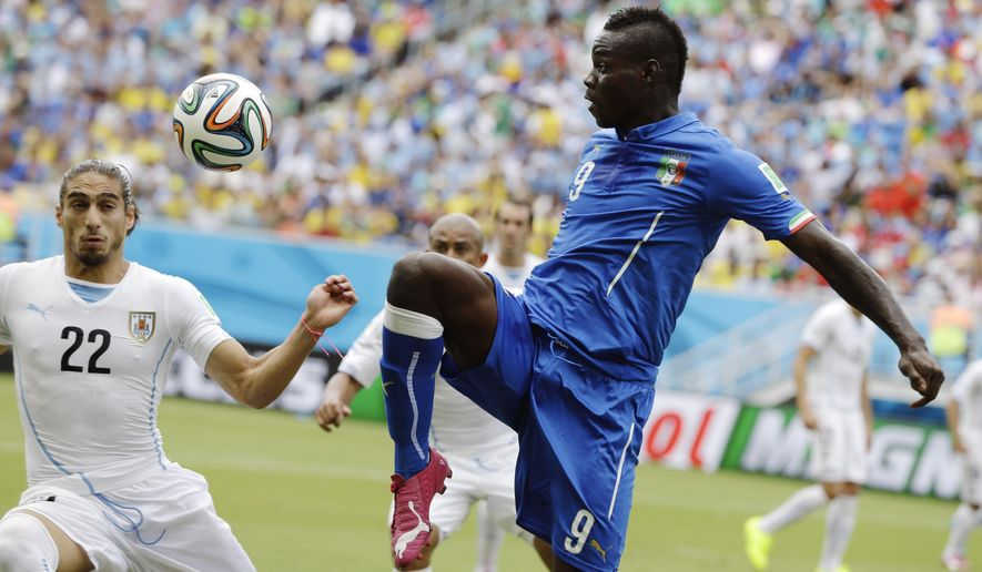 FILE- In this file photo dated  Tuesday, June 24, 2014, Italy's Mario Balotelli, right, kicks the ball over Uruguay's Martin Caceres during the group D World Cup soccer match between Italy and Uruguay at the Arena das Dunas in Natal, Brazil. England's Liverpool soccer club announced Monday Aug. 25, 2014, it has completed the signing of Italy striker Mario Balotelli from AC Milan. (AP Photo/Ricardo Mazalan, FILE)