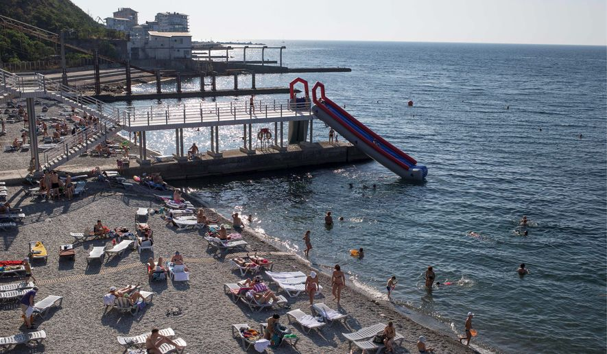 Tourists rest on the Black Sea beach in Yalta, Crimea. Last year the peninsula saw 5.9 million tourists. This summer only about 300,000 visited. (Associated Press)