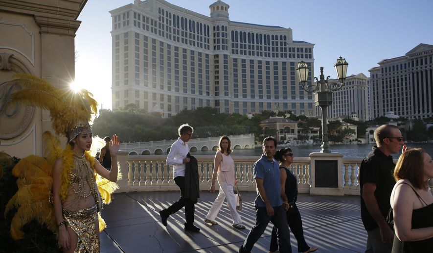 In this Friday, Aug. 15, 2014 photo, people walk by the Bellagio, in Las Vegas. This year, hotels will take in a record $2.25 billion in revenue from fees and surcharges, 6 percent more than in 2013 and nearly double that of a decade ago, according to a new study. Nearly half of the increase can be attributed to new surcharges and hotels increasing the amounts of existing fees. (AP Photo/John Locher)