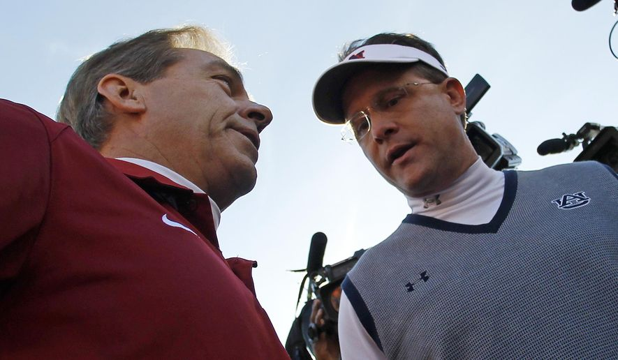 FILE - In this Nov. 30, 2013, file photo, Alabama head coach Nick Saban, left, talks with Auburn head coach Gus Malzahn prior to the start of an NCAA college football game in Auburn, Ala. Saban has had Alabama collecting five-star recruits and national titles with such relentless regularity that some pundits have wondered if he might be college football's best coach ever. Then comes Malzahn, a former Arkansas high school coach who leads the sixth-ranked Tigers to the Southeastern Conference title and national championship game in his first season. (AP Photo/Butch Dill, File)