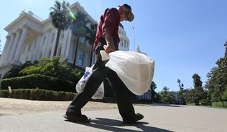 Plastic single-use bags are carried past the State Capitol in Sacramento, California. The California State Legislature on Friday passed a statewide ban on plastic grocery bags. (AP Photo/Rich Pedroncelli)