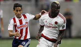 Milan forward Mario Balotelli (45) brings the ball up the field as he is pursued by Guadalajara midfielder Fernando Arce (15) during a soccer match at NRG Stadium Wednesday, Aug. 6, 2014 in Houston. (AP Photo/Bob Levey)