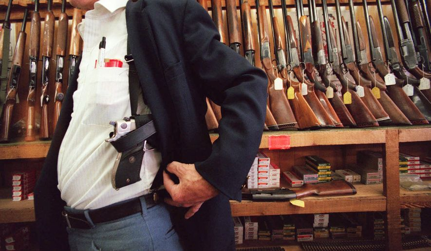 John W. Richardson, owner of Topeka Shooters' Supply in Topeka, Kan., demonstrates a holster that could be used to carry a concealed weapon at his gun shop in this Thursday, April 8, 1999, file photo. (AP Photo/Topeka capital-Journal, Chris Ochsner) ** FILE **