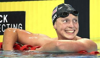 Katie Ledecky of the U.S. smiles after she set a new world record in her women's 1500m freestyle final at the Pan Pacific swimming championships in Gold Coast, Australia, Sunday, Aug. 24, 2014. Ledecky won the race setting a new world record of 15 minutes, 28.36 seconds.(AP Photo/Rick Rycroft)