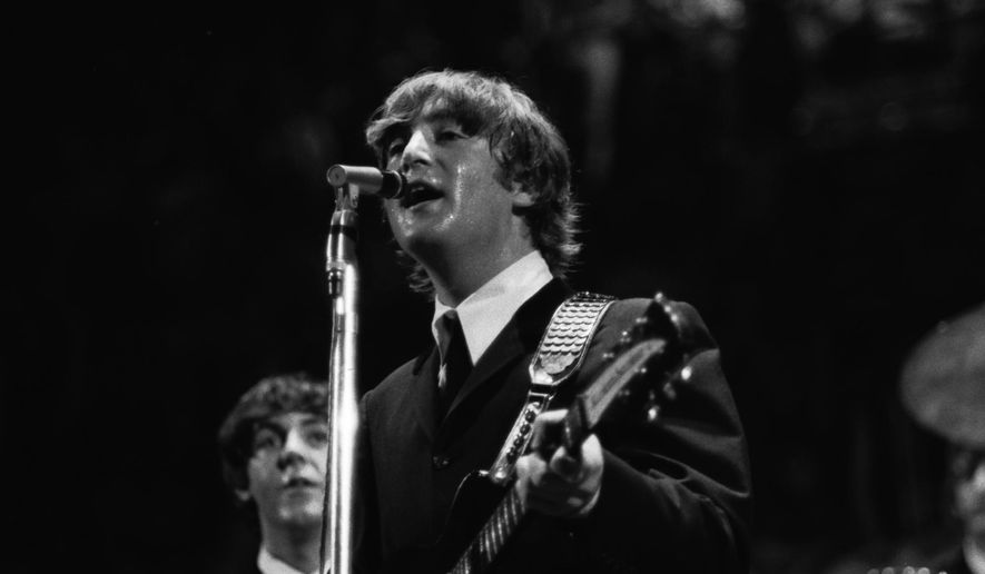 In this 1964 photo made by Walt Burton and provided by Christopher Hoeting, John Lennon, front, and Paul McCartney, of the Beatles, perform during a concert in Cincinnati. Burton, who had special access to the Beatles' 1964 Cincinnati appearance, plans to offer previously unseen photos to the public. (AP Photo/Walt Burton)