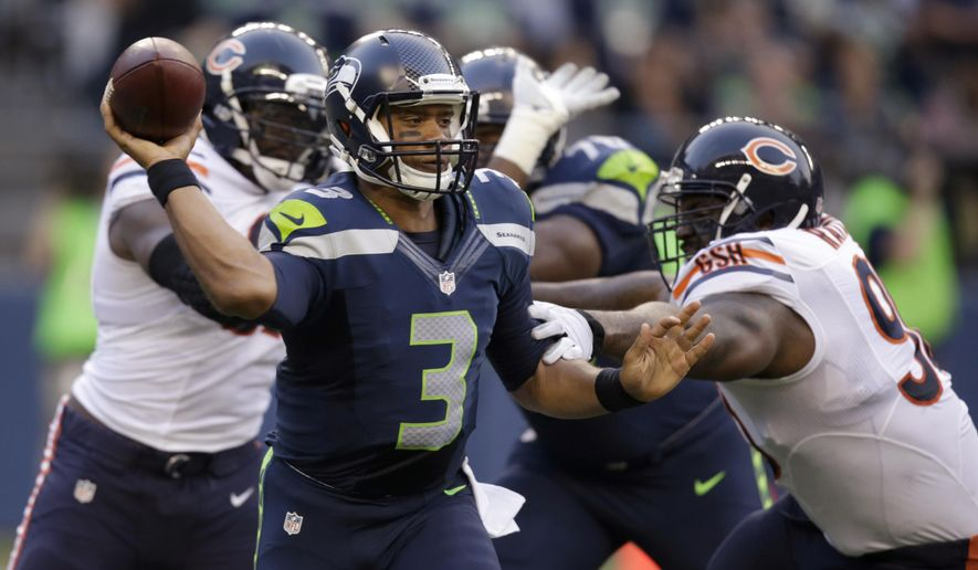 Seattle Seahawks quarterback Russell Wilson passes the ball as Chicago Bears defenders move in during the first half of a preseason NFL football game, Friday, Aug. 22, 2014, in Seattle. (AP Photo/Stephen Brashear)