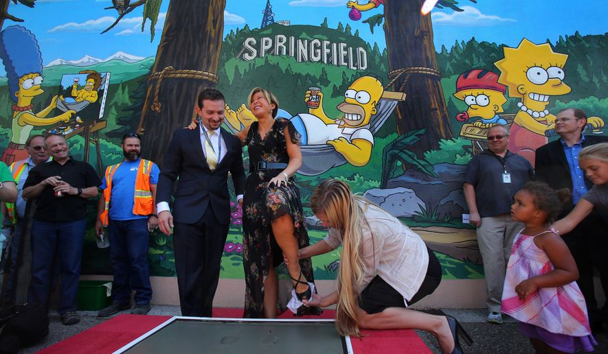 """Actor Yeardley Smith, center, has her shoe wiped off after making her footprints in cement during the unveiling of the new """"The Simpsons"""" mural in Springfield, Ore., Monday, Aug. 25, 2014. Smith, the voice of Lisa Simpson on the long-running animated show """"The Simpsons"""",  kicked off a daylong tribute to the fictional cartoon family after revealing the mural, which was designed by series creator Matt. (AP Photo/The Register-Guard, Brian Davies)"""