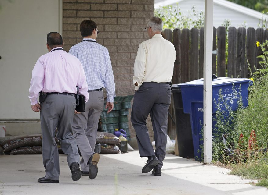 Police walk near garbage cans where a baby was found Tuesday, Aug. 26, 2014, in Kearns, Utah. Police say the newborn, who was left in the trash can near his mother's home, is in extremely critical condition. Unified Police Detective Jared Richardson says a woman who lived nearby heard what she thought was a kitten meowing in the trash bin on Tuesday morning. (AP Photo/Rick Bowmer)