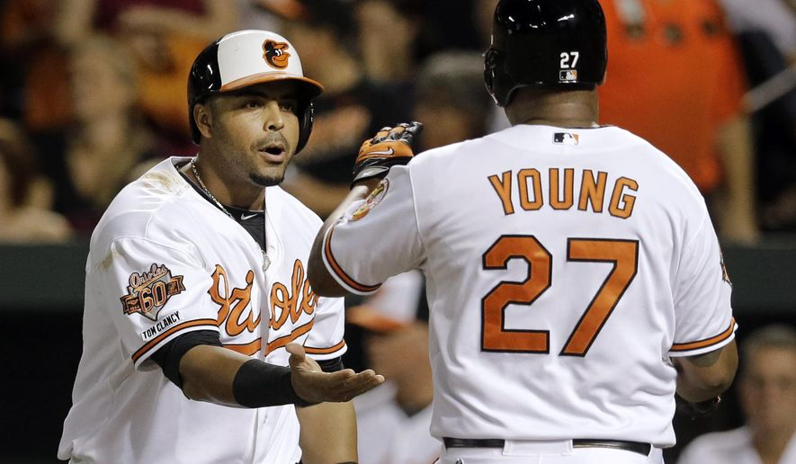 Baltimore Orioles' Nelson Cruz, left, greets teammate Delmon Young at home plate after they scored on a single by Caleb Joseph in the fourth inning of a baseball game against the Tampa Bay Rays, Tuesday, Aug. 26, 2014, in Baltimore. (AP Photo/Patrick Semansky)