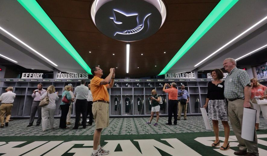 In this Monday, Aug. 25, 2014, photo, Ed Helble, of Okemos, takes a photo of his wife, Charlene, and Rich Pinke, also of Okemos, during a tour of the new North End Zone Complex renovations at Spartan Stadium in East Lansing on the Michigan State Campus. (AP Photo/Detroit Free Press, Ryan Garza)  DETROIT NEWS OUT, TV OUT, INTERNET OUT, MAGS OUT, NO SALES, MANDATORY CREDIT DETROIT FREE PRESS