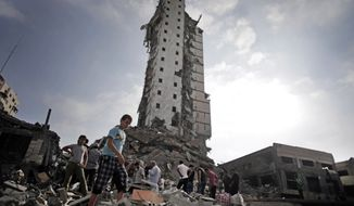 Palestinians inspect the damage to the Italian Complex following several late night Israeli airstrikes in Gaza City, Tuesday, Aug. 26, 2014. Israel bombed two Gaza City high-rises with dozens of homes and shops Tuesday, collapsing the 15-story Basha Tower and severely damaging the Italian Complex in a further escalation in seven weeks of cross-border fighting with Hamas. (AP Photo/Khalil Hamra)