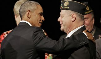 President Barack Obama greets a legionnaire after speaking at the American Legion national convention in Charlotte, N.C., Tuesday, Aug. 26, 2014. Three months after a veterans' health care scandal rocked his administration, President Barack Obama is taking executive action to improve the mental well-being of veterans. The president was to announce his initiatives during an appearance before the American Legion National Convention that is fraught with midterm politics. (AP Photo/Chuck Burton)