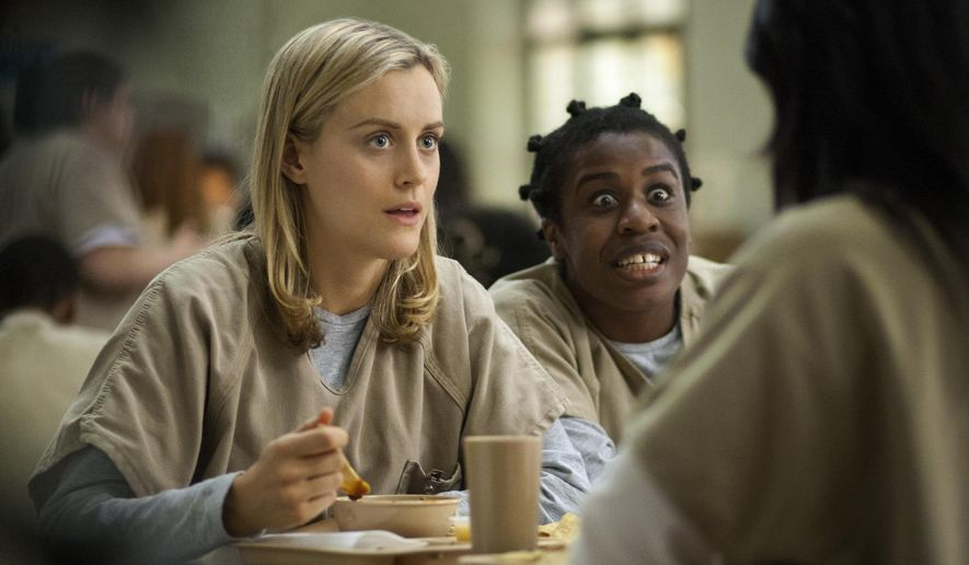 """FILE - This image released by Netflix shows Taylor Schilling, left, and Uzo Aduba in a scene from """"Orange Is the New Black."""" Americans are increasingly engaging in a practice known as television binge-watching _ going through several episodes in a single stretch, rather than one a week, as was common before the advent of digital video recorders and Internet streaming services such as Netflix and Hulu. (AP Photo/Netflix, Paul Schiraldi, File)"""