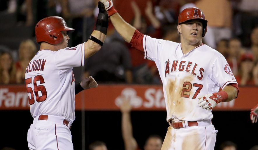 Los Angeles Angels' Mike Trout, right, celebrates with Kole Calhoun after scoring on a hit by Albert Pujols during the fourth inning of a baseball game against the Miami Marlins in Anaheim, Calif., Tuesday, Aug. 26, 2014. (AP Photo/Chris Carlson)