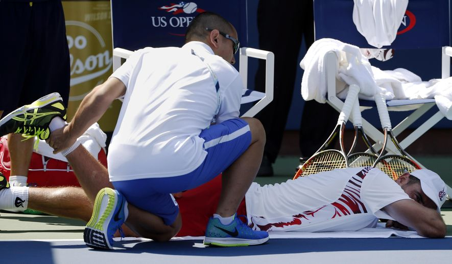 Ivan Dodig, of Croatia, is treated by a trainer during an injury timeout during the second round of the 2014 U.S. Open tennis tournament against Feliciano Lopez, of Spain, Wednesday, Aug. 27, 2014, in New York. Dodig forfeited the match to Lopez in the fifth set. (AP Photo/Kathy Willens)