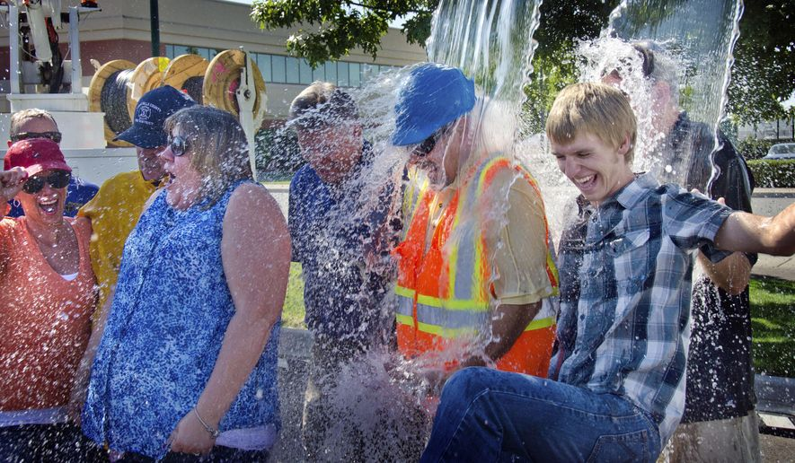 """In this photo taken on Tuesday, Aug. 26, 2014, Ten Pocket iNet corporation employees, from left,including Terri McMakin, Don Gibbard, weargin hard hat, and Jake Tegtmeier, right, take the ice bucket challenge at the Walla Walla Regional Airport in Walla Walla, Wash.to benefit ALS research. The water was poured from two lift trucks. Gibbard said he wore his hard hat to protect from the ice cubes and took the brunt of dousing because """"I was pulled back!"""" (AP Photo/Walla Walla Union-Bulletin, Greg Lehman)"""