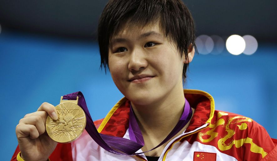 FILE - In this July 31, 2012 file photo, China's Ye Shiwen poses with her gold medal for the women's 200-meter individual medley swimming final at the Aquatics Centre in the Olympic Park during the 2012 Summer Olympics in London. The 2012 London Games champion in the women's 200- and 400-meter medleys registered late August, 2014 at Beijing's prestigious Tsinghua University under a government program waiving the grueling entrance exam for outstanding athletes. (AP Photo/Matt Slocum, File)