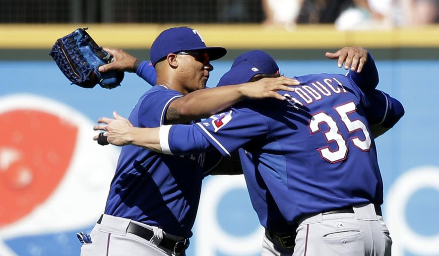 Texas Rangers outfielders Michael Choice, left, Leonys Martin and Jim Adduci gather for a group hug after the team beat the Seattle Mariners in a baseball game Wednesday, Aug. 27, 2014, in Seattle. The Rangers won 12-4. (AP Photo/Elaine Thompson)