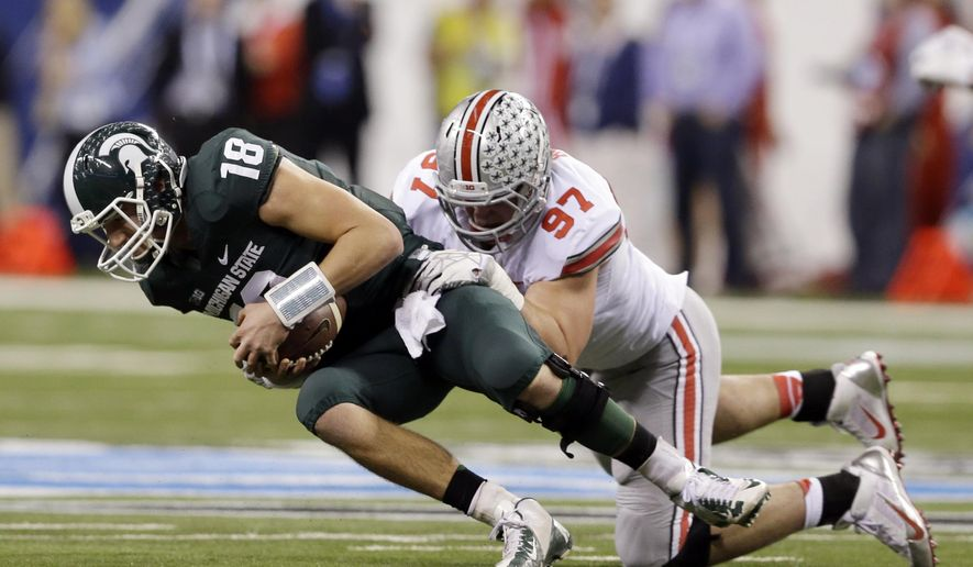 FILE - In this Dec. 7, 2013, file photo, Michigan State's Connor Cook (18) is sacked by Ohio State's Joey Bosa (97) during the first half of a Big Ten Conference championship NCAA college football game in Indianapolis. For Saturday's, Aug. 30, 2014, season opening game with Navy, Bosa and the Ohio State defense must get ready for the Midshipmen's lethal triple-option game. (AP Photo/Darron Cummings, File)