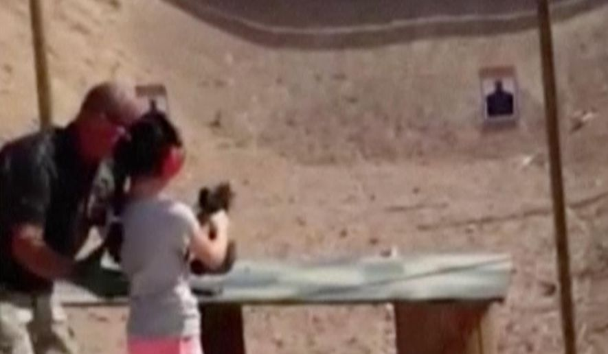 In this Aug. 25, 2014 image made from video provided by the Mohave County Sheriff Department, firing-range instructor Charles Vacca, left, shows a 9-year old girl how to use an Uzi. Vacca, 39, was standing next to the girl on Monday at the Last Stop range in Arizona, south of Las Vegas, when the girl squeezed the trigger, causing the Uzi to recoil upward and shoot Vacca in the head. (AP Photo/Mohave County Sheriff Department)