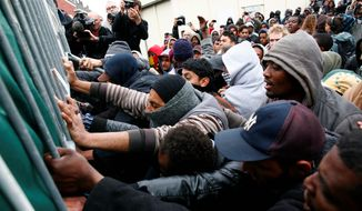 Seeking asylum: Migrants and activists scuffle with police after authorities started to clear out makeshift camps in Calais, France on the English Channel. Officials blame a British-French pact for burdening the city with immigrants seeking British asylum. (Associated Press)