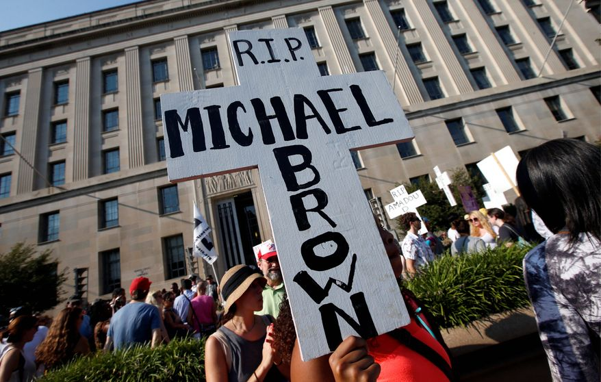 Christina Bijou, from Greenbelt, Maryland, rallies outside the Department of Justice to call on the Attorney General Eric H. Holder Jr. to help secure justice for Michael Brown.