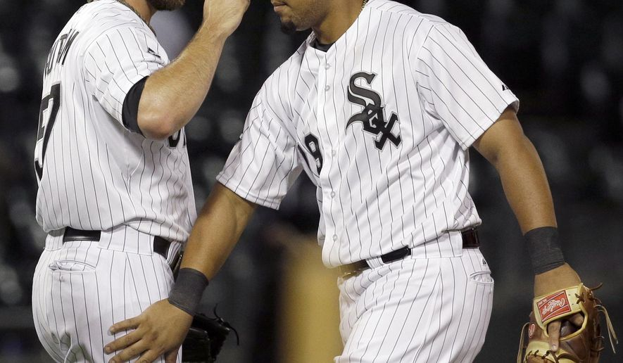 Chicago White Sox's Jose Abreu (79), right, celebrates with relief pitcher Zach Putnam (57), after the White Sox defeated the Cleveland Indians 3-2 in a baseball game in Chicago, Wednesday, Aug. 27, 2014. (AP Photo/Nam Y. Huh)