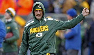FILE - In this Nov. 24, 2013 file photo, Green Bay Packers quarterback Aaron Rodgers stretches his arm during warm ups prior to an NFL football game against the Minnesota Vikings in Green Bay, Wis. Rodgers sure looks like he's ready to go during the brief spurts of Packers practice open to media. But whether the franchise quarterback will be cleared from a left collarbone injury in time to play Sunday, Dec. 22, 2013, against the Steelers remains in question.(AP Photo/Matt Ludtke, File)
