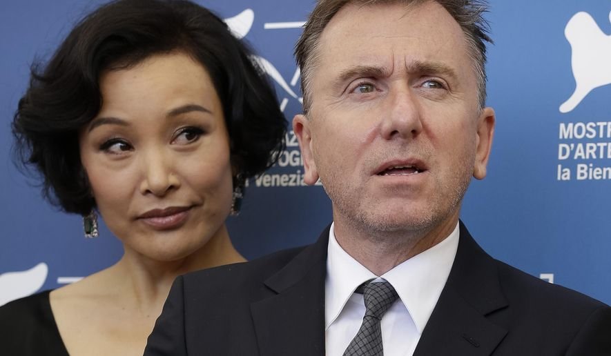 Members of the Venice 71 Jury, Joan Chen, left, and Tim Roth pose during a photo call at the 71st edition of the Venice Film Festival in Venice, Italy, Wednesday, Aug. 27, 2014. (AP Photo/Andrew Medichini)