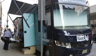 **FILE** In this photo taken on Tuesday, Aug. 26, 2014, Project Child Support employees offer low-cost legal advice to parents from a refurbished RV parked outside Essex County Family Courthouse in Newark, N.J. (AP Photo/Rachelle Blidner)