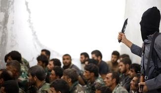 A fighter from the Islamic State group, armed with a knife and an automatic weapon, next to captured Syrian army soldiers and officers, following the battle for the Tabqa air base, in Raqqa, Syria, Aug. 27, 2014. (Associated Press) ** FILE **