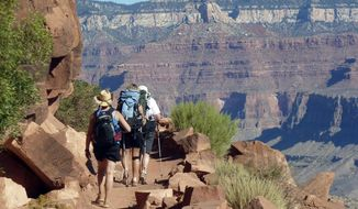 """FILE-This Monday, Sept. 27, 2010 file photo shows hikers on the South Kaibab Trail in Grand Canyon National Park, Ariz. The Grand Canyon is imposing new restrictions on hikers who are turning up in larger numbers to complete grueling """"rim to rim"""" excursions from one end of the canyon to the other. The popularity of the hikes have created problems with litter and safety as people need to be rescued. (AP Photo/Carson Walker, file)"""