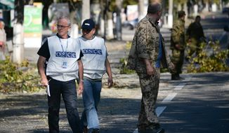 Members of the OSCE examine the scene of a shelling in the town of Donetsk, eastern Ukraine, Wednesday, Aug. 27, 2014. The Obama administration accused Russia on Wednesday of orchestrating a new military campaign in Ukraine, helping rebel forces expand their fight in the country's east and sending tanks, rocket launchers and armored vehicles toward communities elsewhere. (AP Photo/Mstislav Chernov)
