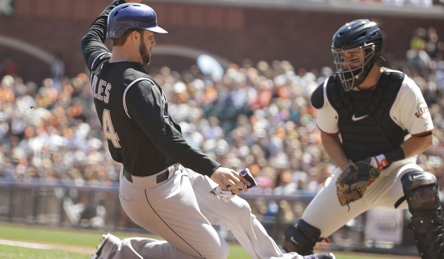 Colorado Rockies' Jordan Lyles, left, scores the Rockies' first run as San Francisco Giants catcher Andrew Susac, right, waits to make the late tag in the third inning of their baseball game Thursday, Aug. 28, 2014, in San Francisco. Lyles scored after the Rockies' Charlie Blackmon hit a line drive to left field. (AP Photo/Eric Risberg)