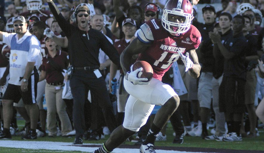 New Mexico State wide receiver Teldrick Morgan glances back while running in a 30-yard touchdown reception against Cal Poly during an NCAA college football game Thursday, Aug. 28, 2014, in Las Cruces, N.M. (AP Photo/Las Cruces Sun-News, Robin Zielinski)