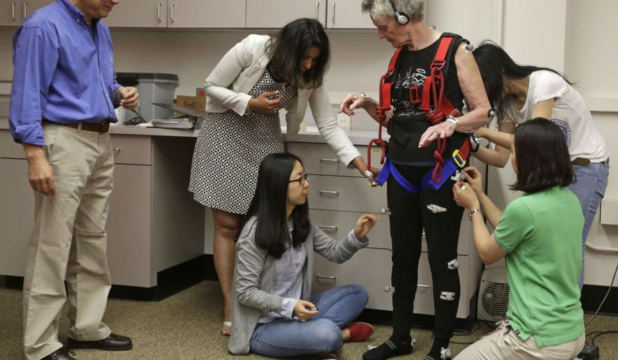 """This July 28, 2014 photo shows Clive Pai, a University of Illinois, Chicago physical therapy professor, left, watching as researchers affix sensors to Mary Kaye, 81 before she demonstrates a treadmill balance session at the school in Chicago. Kaye, who is supported by a safety harness, walks on a lab-built walkway that causes people to unexpectedly trip and can teach them quickly how to catch themselves and avoid falling. Falls in the elderly cost $30 billion yearly to treat and can send them spiraling into poor health and disability. Pai who came up with the idea calls it """"a vaccine against falls"""" and says his research shows that older people's brains can learn and adapt much more quickly than previously thought. (AP Photo/M. Spencer Green)"""