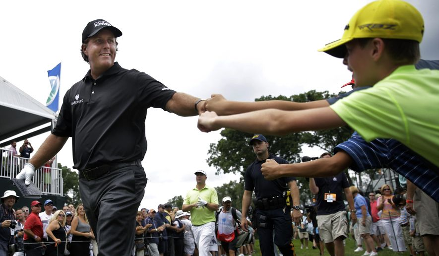Phil Mickelson greets fans as he walks on the course during the second round of play at The Barclays golf tournament Friday, Aug. 22, 2014, in Paramus, N.J.  (AP Photo/Mel Evans)