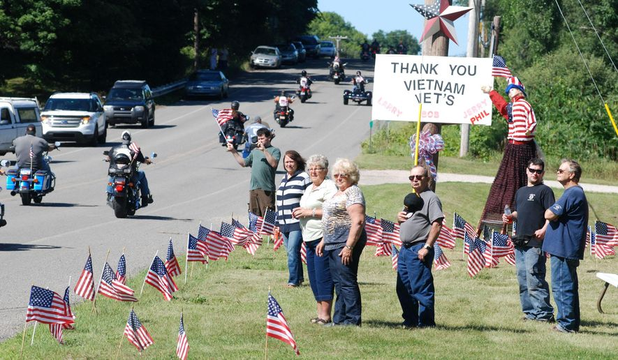 Approximately 300 motorcyclists escort the Cost of Freedom Vietnam Traveling Wall to Ludington City Park, Ludington, Mich. from the Oceana Fairgrounds in Hart, Mich., Wednesday, Aug. 27, 2014. The bikes pass the Alta Petersen resident on South Pere Marquette Highway where family and friends gathered near the display they made honoring Vietnam veterans in their family or friends of the family. The traveling wall will be on display in Ludington through noon Sunday, Aug. 31, 2014. (AP Photo/The Ludington Daily News, Steve Begnoche)