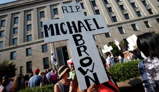 Christina Bijou, from Greenbelt, Maryland, rallies outside the Department of Justice to call on the Attorney General Eric H. Holder Jr. to help secure justice for Michael Brown. (Alex Brandon)