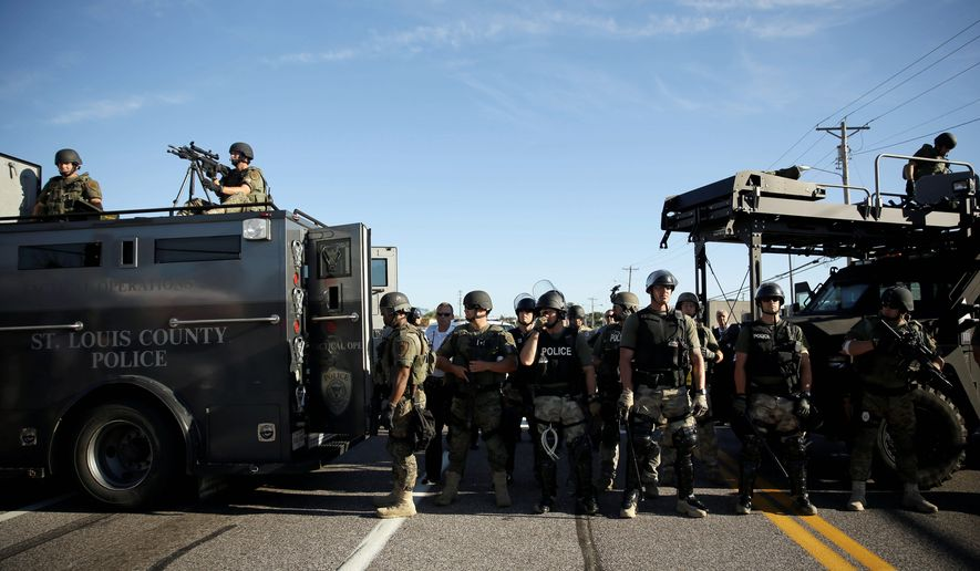 Police in riot gear watch protesters in Ferguson, Missouri. The transfer program is under intense scrutiny in the aftermath of this month's standoffs between police and protesters. (Associated Press photographs)