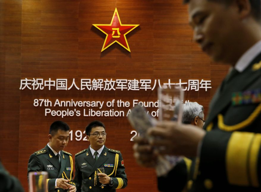 Guests from the Chinese People's Liberation Army attend a reception at the Central Barracks in Hong Kong on July 31 to celebrate the 87th anniversary of its founding. Some fear the Aug. 25 incident at Huangcang High School could spark backlash. Nothing would pose a worse nightmare for the Communist Party if the PLA once again were to become the enemy of the Chinese people in the public's perception.(AP Photo/Kin Cheung)