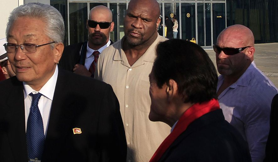 "Former NFL player Bob ""The Beast"" Sapp, center, arrives at the Sunan International Airport, Thursday, Aug. 28, 2014 in Pyongyang, North Korea. Sapp is participating in a two-day martial arts extravaganza in Pyongyang over the weekend organized by Japanese pro-wrestler turned politician Kanji ""Antonio"" Inoki in an oddball attempt at sports diplomacy. (AP Photo/Jon Chol Jin)"