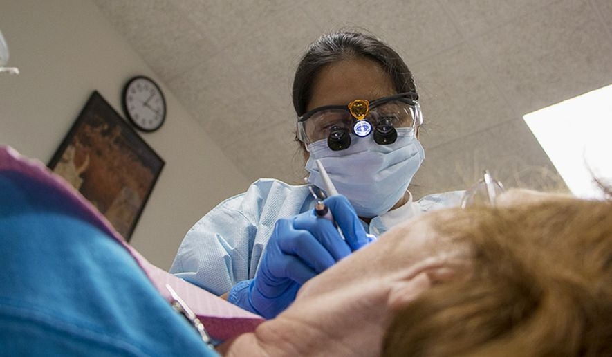 ADVANCE FOR USE SATURDAY, AUG. 30 AND THEREAFTER - In this July 22, 2014 photo, Dipal Patel, a dental hygiene student, examines the mouth of a patient at the Dental Hygiene Clinic at Lake Land Community College in Mattoon, Ill. At the Mattoon campus, students try their trade on patients who want their teeth cleaned, polished and flossed at a low cost. They are required to follow a strict set of procedures, recording each step of the process. (AP Photo/Herald & Review, Amanda Wilkinson)
