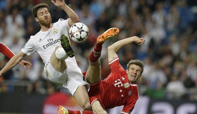 Real's Xabi Alonso, left, and Bayern's Thomas Mueller challenge for the ball during a  Champions League semifinal first leg soccer match between Real Madrid and Bayern Munich at the Santiago Bernabeu stadium in Madrid, Spain, Wednesday, April 23, 2014 .(AP Photo/Paul White)