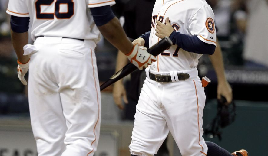 Houston Astros' Jose Altuve (27) crosses home plate in front of teammate Jon Singleton (28) to score from third base on a wild pitch from Oakland Athletics reliever Ryan Cook in the sixth inning of a baseball game Wednesday, Aug. 27, 2014, in Houston. (AP Photo/Pat Sullivan)