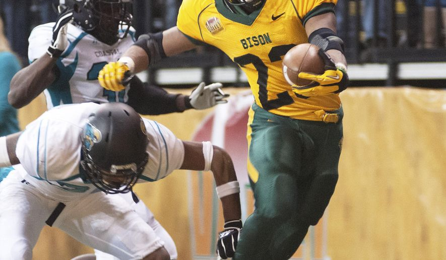 FILE - In this Dec. 14, 2013 file photo, North Dakota State running back John Crockett (23) is knocked out-of-bounds short of the goal line by Coastal Carolina defenders in an NCAA college football game in the quarterfinals of the Football Championship Subdivision playoffs in Fargo, N.D. The Bison are on a quest for a fourth straight Football Championship Subdivision title. They open their season Saturday, Aug. 30 against Iowa State in Ames, Iowa. (AP Photo/Kevin Cederstrom, File)
