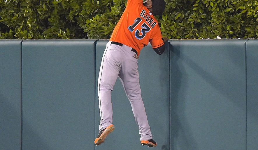 Miami Marlins center fielder Marcell Ozuna can't reach a solo home run by Los Angeles Angels' Mike Trout during the seventh inning of a baseball game, Wednesday, Aug. 27, 2014, in Anaheim, Calif. (AP Photo/Mark J. Terrill)