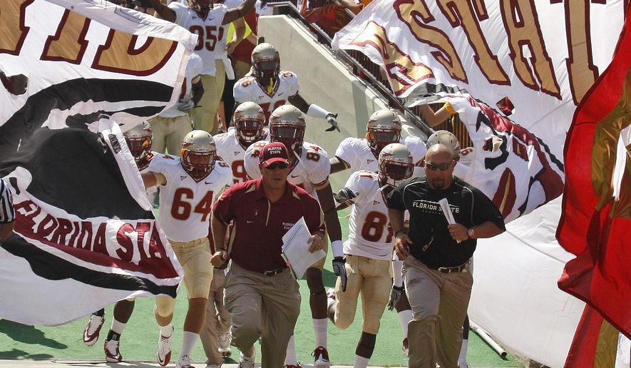 FILE - In this Sept. 11, 2010, file photo, Florida State players and coaches run onto the field before an NCAA college football game against Oklahoma in Norman, Okla. A new era in college football is here. After years of deriding the BCS, fans will finally get what they wanted with the new College Football Playoff. The top-ranked Seminoles open the season on Saturday against Oklahoma State in Arlington, Texas.  (AP Photo/Sue Ogrocki, File)