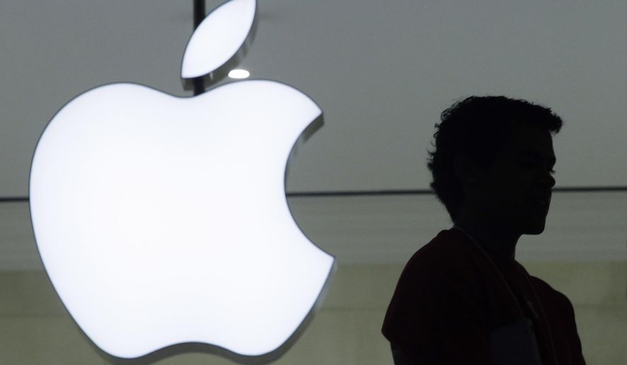 In a Wednesday, Dec. 7, 2011, file photo, a person stands near the Apple logo at the company's store in Grand Central Terminal, in New York. (AP Photo/Mark Lennihan, File)